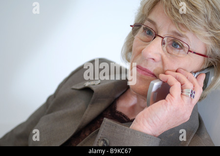 mature businesswoman talking on mobile phone looking concerned - Stock Photo