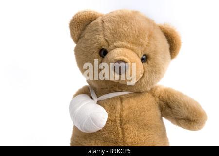 Toy bear with a broken leg - Stock Photo