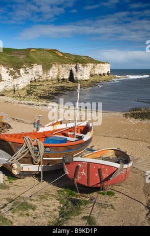 Fishing Boats moored at North Landing with beach and chalk cliffs beyond on the Flamborough Headland Heritage Coast, - Stock Photo