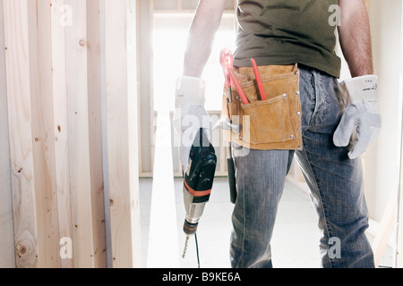 detail of young man with electric drill and other construction tools - Stock Photo