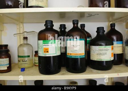 Hazardous chemicals on a shelf in a laboratory - Stock Photo