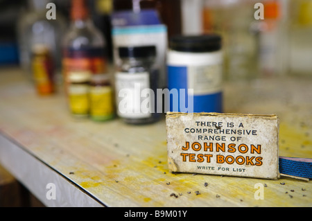Box of Johnson Test books on a messy laboratory bench, with bottles and jars of chemicals in the background. - Stock Photo