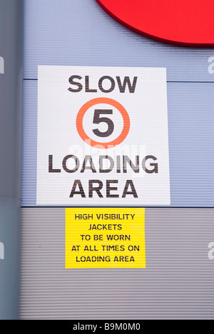 Signs in a loading area stating 5mph speed limit and high visibility jackets to be worn at all times - Stock Photo