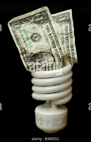 Energy saving lightbulb with two crumpled dollar bills stuck in the top in front of a black background - Stock Photo
