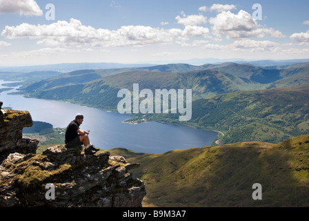 A hiker looks out at the stunning view from the summit of Ben Lomond on a bright sunny day, Stirlingshire, Scotland - Stock Photo