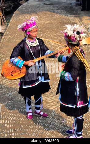 China, Guizhou province, Zhaoxing, young girls of the Dong ethnic group, playing a tradtional instrument - Stock Photo