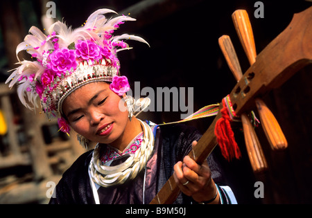 China, Guizhou province, Zhaoxing, young girl of the Dong ethnic group, playing a tradtional instrument - Stock Photo