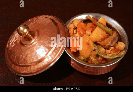 A bowl of vegetable curry on a dark wooden table. - Stock Photo