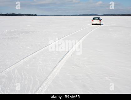 Toyota Avensis 2007 sedan driving on frozen lake ice . Lake Keitele , Finland - Stock Photo