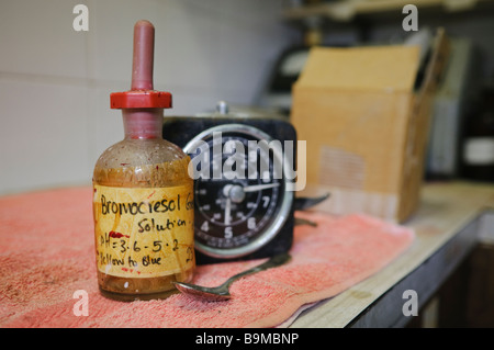 Old laboratory stopwatch/timer with a dropper bottle labelled 'Bromocresol solution, pH 3.6-5.2, yellow to blue' - Stock Photo