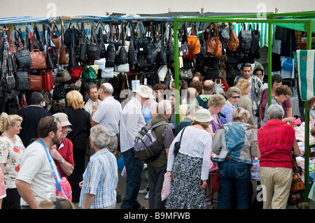 Tourists hunting for a bargain in popular Los Cristianos Sunday market with leather goods on display Tenerife Canary - Stock Photo