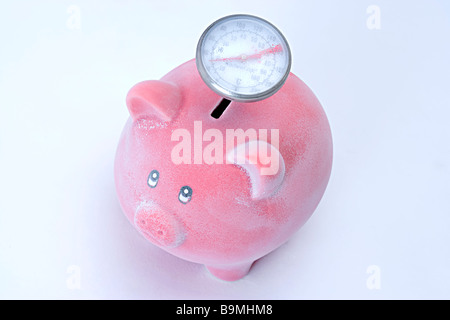 Pink frozen icy piggy bank with thermometer sticking out the top depicting low interest rates or frozen economy - Stock Photo