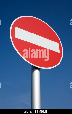 British red and white no entry road sign with a blue sky. - Stock Photo