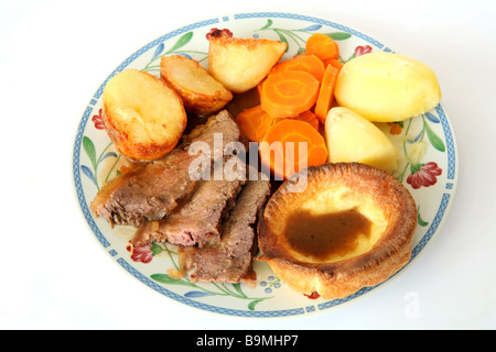 Traditional British Sunday lunch of roast beef,Yorkshire pudding,roast and boiled potato,carrots and gravy - Stock Photo