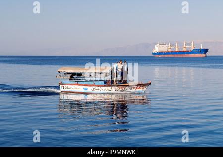 Jordan, Al Aqaba Governorate, Al Aqaba City, cargo and touristic boat view from the marina harbour - Stock Photo