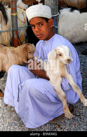 Worried Omani boy tenderly holds a goatling in his arms, Nizwa, Sultanate of Oman - Stock Photo
