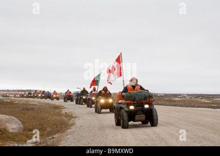 Dirt track with row of Canadian Rangers and canadian flag on quad bikes, Canadian Arctic, Canada - Stock Photo