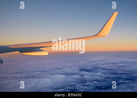 View through airliner window high above clouds at sunrise - Stock Photo