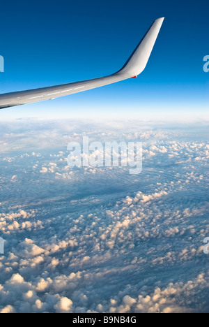 View through airliner window high above clouds - Stock Photo