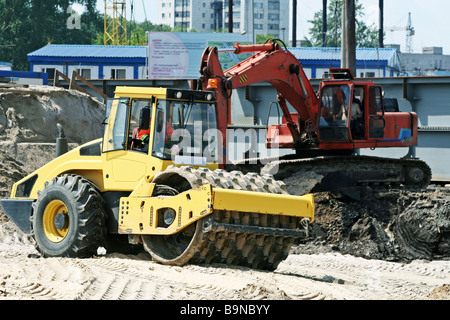 Road roller and excavator. - Stock Photo