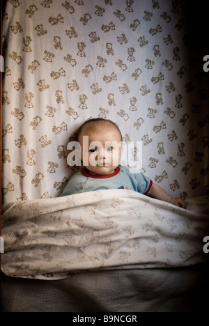 Baby in cot - Stock Photo
