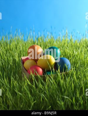 colored Easter eggs in basket in the the grass - Stock Photo