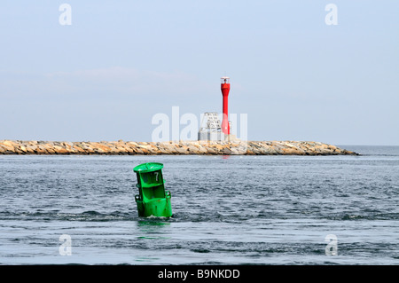 Navigational channel markers in ocean with a green can and a red solar powered daymarker on stone jetty. - Stock Photo