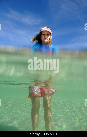 A six year old girl stands in crystal clear water at Geordie Bay on Rottnest Island , Western Australia. - Stock Photo