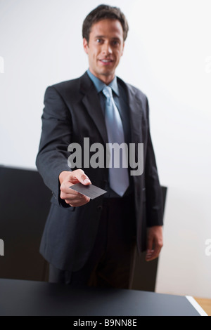 portrait of businessman handing out his business card - Stock Photo