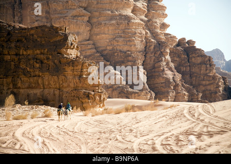 two tourists riding camels in the desert, Wadi Rum Jordan, Middle East - Stock Photo