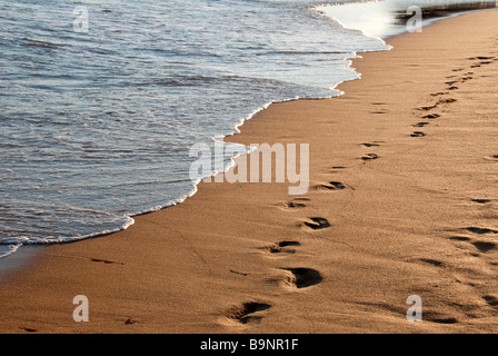 Footprints in wet sand as a wave starts to wash over them - Stock Photo