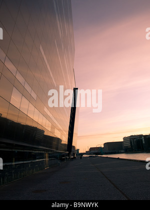 Sunrise in Copenhagen, Denmark.  The Royal Library (the Black Diamond) towers to the left, blending into the morning - Stock Photo