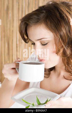 woman drinking herbal tea in bedroom - Stock Photo