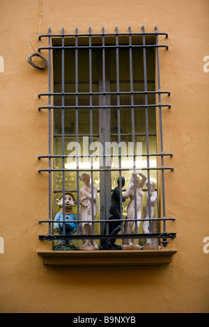 Reproductions of classical statues and a figure of Dopey from the Walt Disney film Sleeping Beauty on a window in - Stock Photo