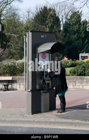 Essex Girl with long black hair using public street BT telephone box, making a call, Romford, Essex, UK, Europe, - Stock Photo