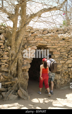 Tourists couple at ancient Mayan ruined walled town Tulum Yucatan entering through Mayan arch in the walls - Stock Photo