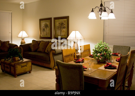 Living room with cushions on couches with coffee table and adjoining dining area - Stock Photo