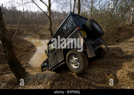 A Land Rover Defender 90 creeps down a steep bank - Stock Photo