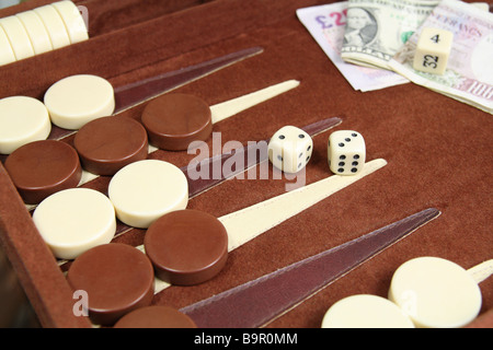 Backgammon game in progress showing checkers, dice and wager. - Stock Photo