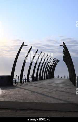 Senior couple in silhouette strolling along a pier at dawn. Durban, Kwazulu Natal, South Africa. - Stock Photo