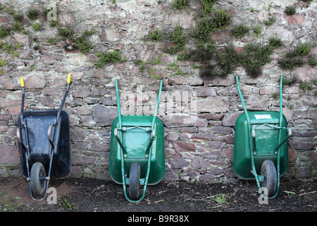 wheelbarrows leaning against a wall - Stock Photo