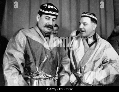 Josef Stalin left and Kliment Voroshilov right wearing ethnic costumes presented to them by delegates from a conference - Stock Photo