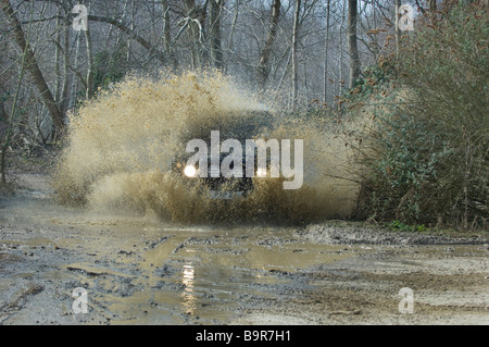 A Land Rover Defender 90 splashes through a flooded track in woodland in Slindon West Sussex UK during an Off Road - Stock Photo