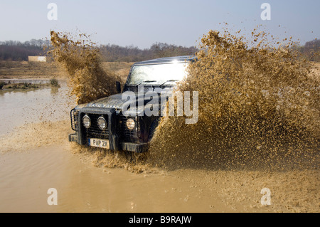 A Land Rover Defender 90 speeds through a flooded road in Slindon West Sussex UK during an Off Road exercise - Stock Photo