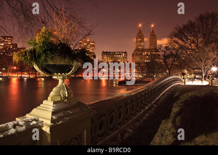 View of Central Park West the Lake and Bow Bridge from Bow Bridge in Central Park New York City at dusk - Stock Photo