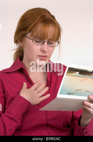 A woman reading a card that has conveyed some news that has made her sad or emotional - Stock Photo