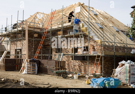 Building site of a new house in the process of having the roof constructed. - Stock Photo