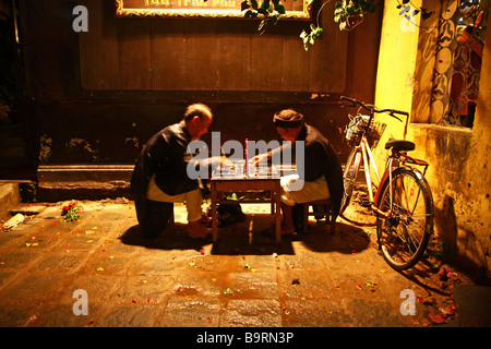 Street night scene. Two old men playing chess in the street of Hoi An. Vietnam, Sout East Asia - Stock Photo