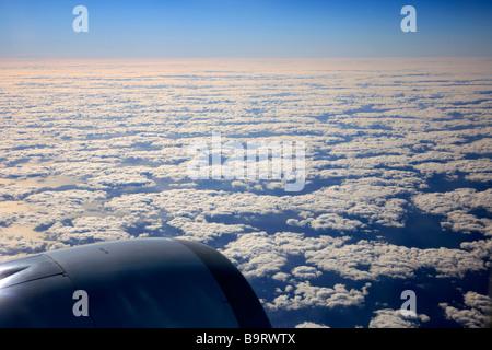 View from Aeroplane window of McDonald Douglas MD-11 jet engine over Atlantic Ocean with Nimbostratus clouds - Stock Photo