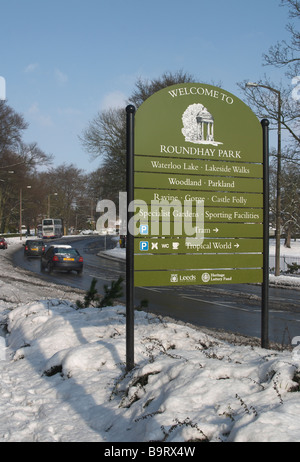 Snow scene with trees and shrubs and hedge Road running through with Welcome to Roundhay Park sign - Stock Photo